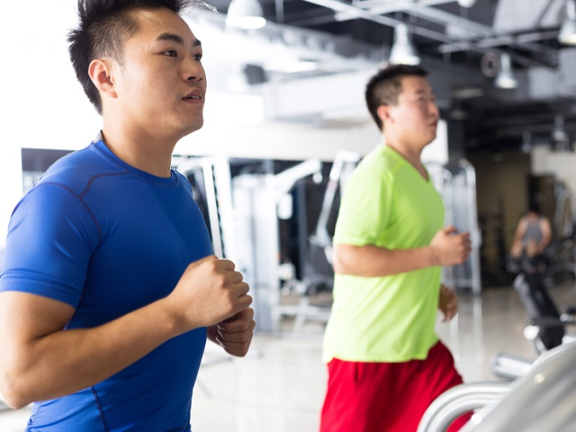 group of women and men running on treadmill in gym or fitness club