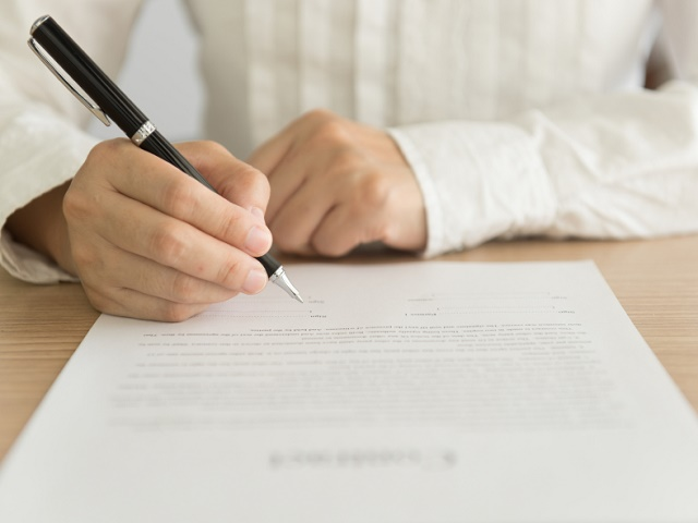 hand holding a pen to sign approval about to sign a letter