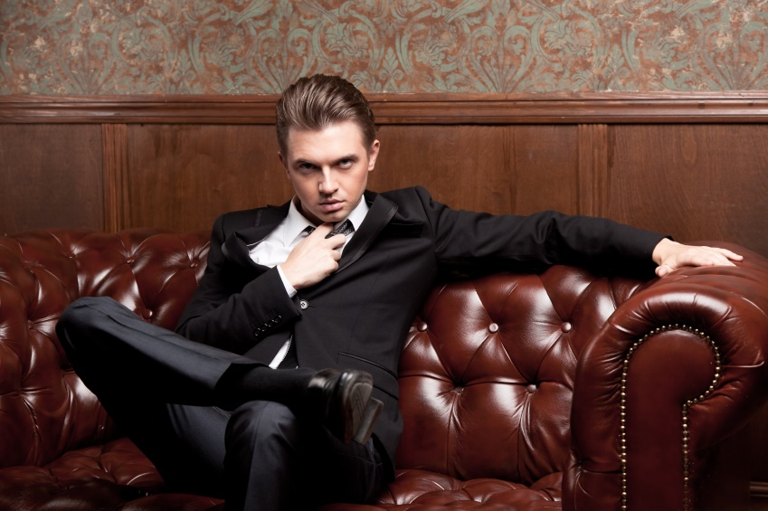 attractive young man in a suit sitting on couch
