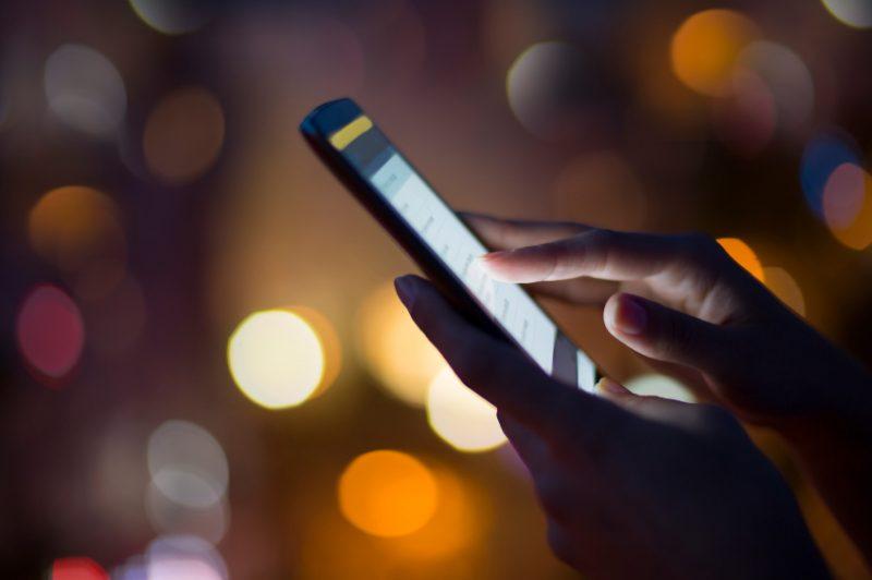 Woman using her mobile phone , city skyline night light  backgro