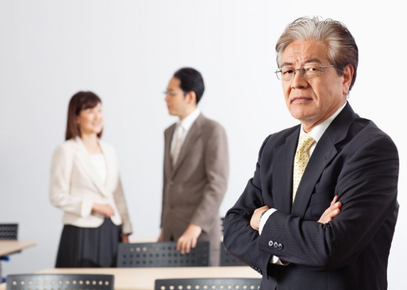 Businessman standing with arms crossed and colleagues in the background