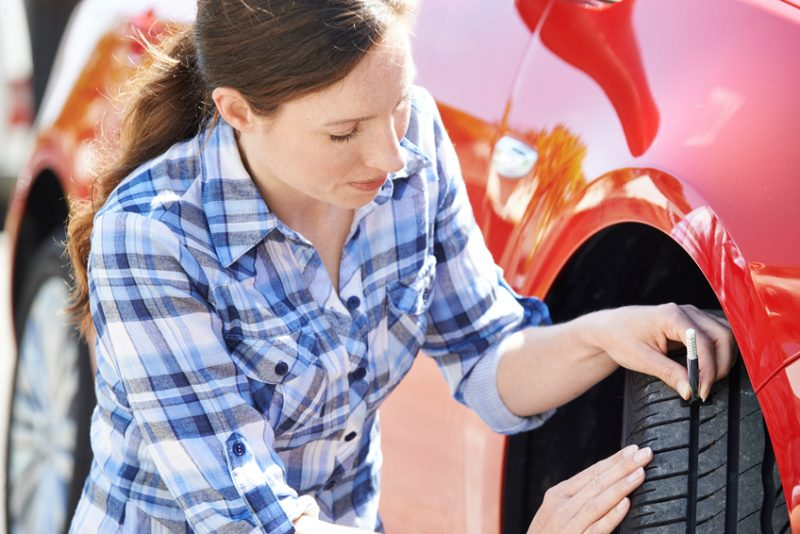 Woman Checking Tread On Car Tyre With Gauge