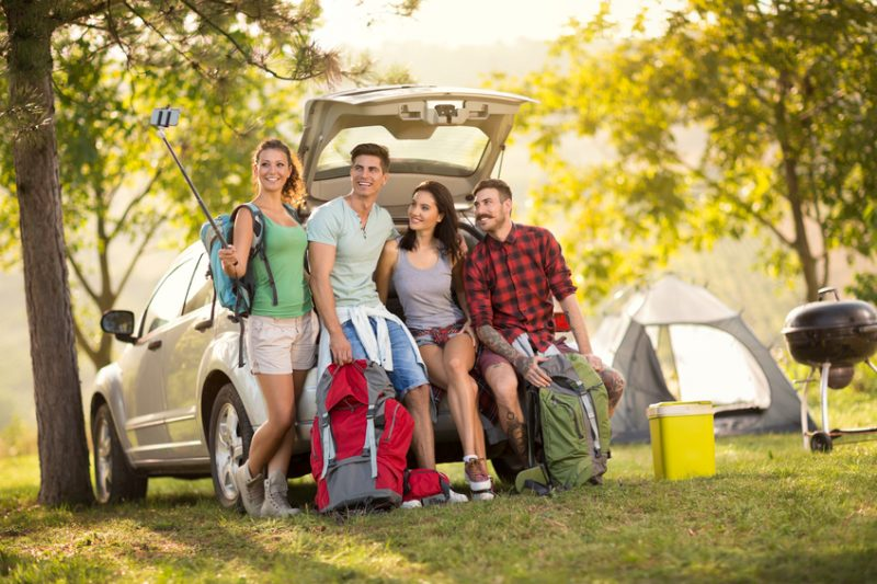group of friends taking selfie with smartphone on camping trip
