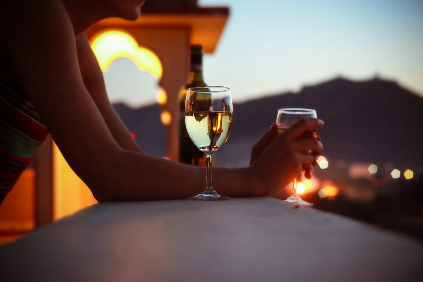 Woman on exotic vacation drinking white wine at sunet. Close up of wine glass. Unrecognizable person.