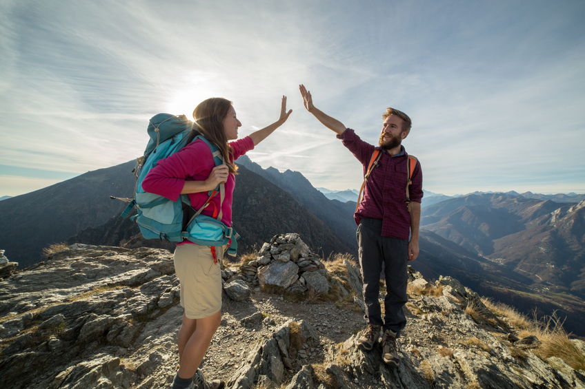 Couple of hikers reaches mountain top, celebrates with high five.