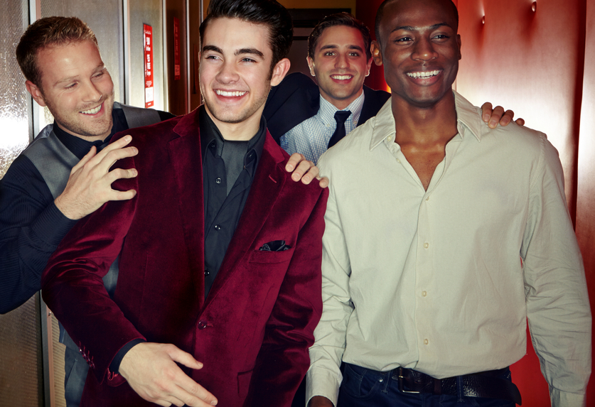 A group of smartly dressed men arriving at a nightclub together