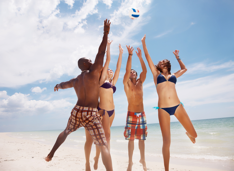 Group of multi ethnic friends playing volleyball on beach against sky