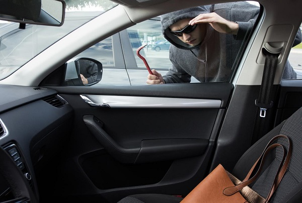 Thief wearing black hooded jacket and sunglasses is looking for unattended valuables left in a car.