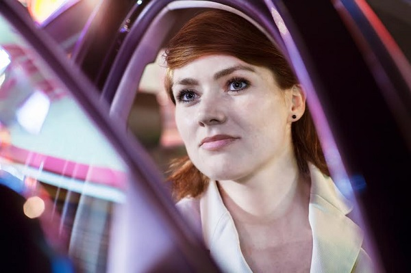 Serene businesswoman opening car door at night, close-up, reflected lights