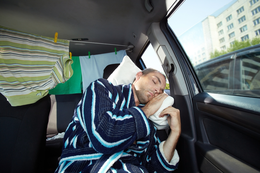 Young man in bathrobe sitting in his car and sleeping during traffic jam