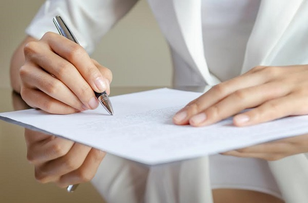 close-up of woman's hands signing a contract