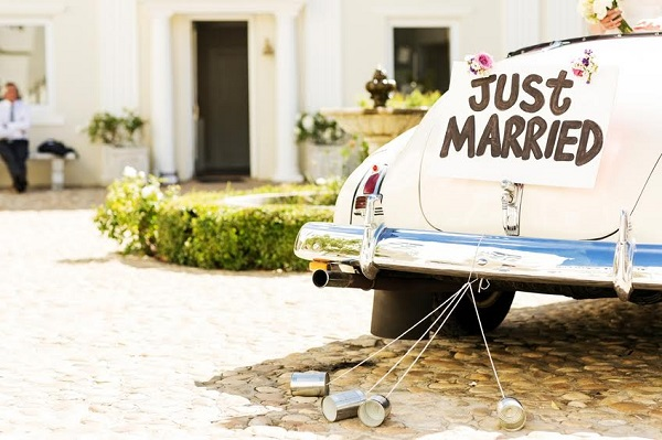 Just married sign and cans attached to convertible car. Horizontal shot.