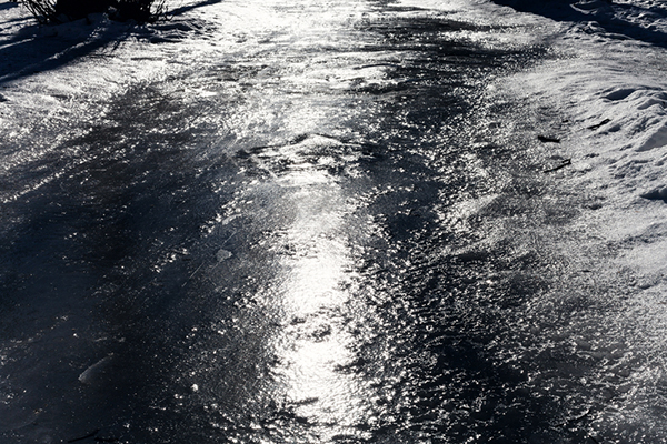 ice on frozen footpath in cold winter day